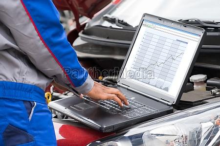 mechanic using laptop for examining car