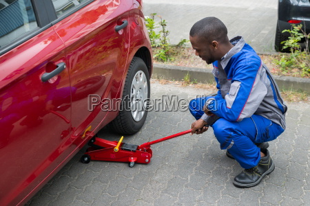 mechanic putting hydraulic floor jack inside