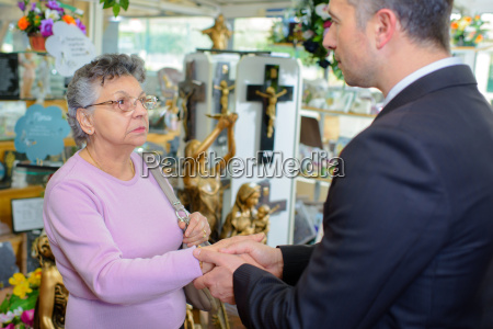 woman with undertaker amongst memorial artefacts