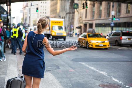 girl callinghailking taxi cab on manhattan