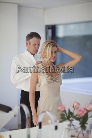 mature man adjusting necklace of woman