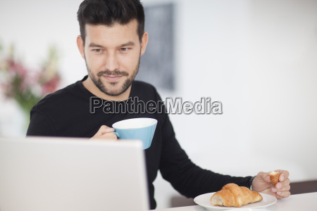 mid adult man looking at laptop