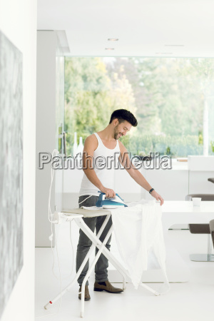 mid adult man ironing clothes at