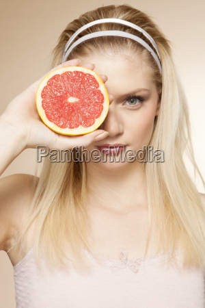 portrait of young woman holding grapefruit