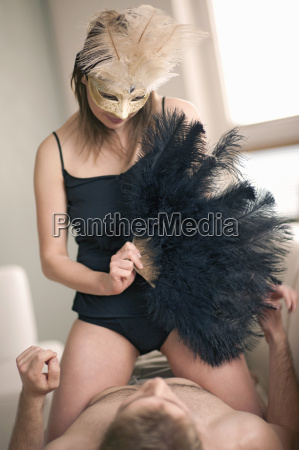 young woman wearing mask and holding