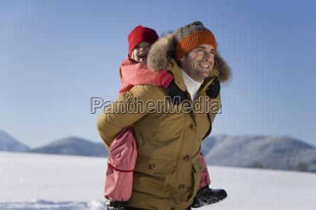 man carrying daughter through snow