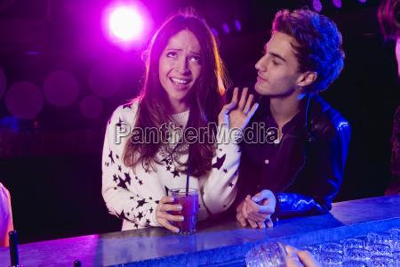young man bothering woman at bar