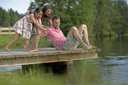 mother and daughter pushing father on