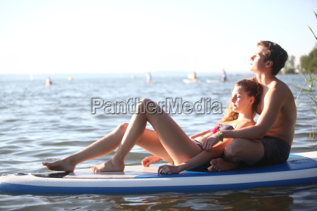 teenage couple sunbathing on paddleboard on