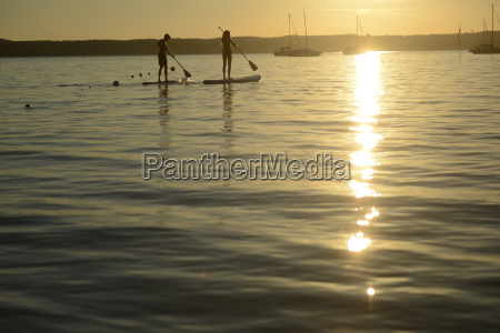 teenage couple paddle boarding at sunset