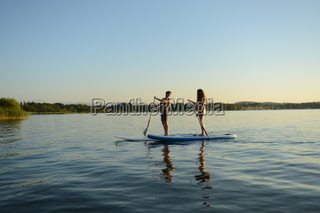 teenage couple paddle boarding on lake