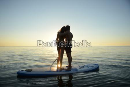 teenage couple watching sunset from paddleboard
