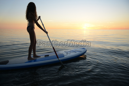 teenage girl on paddleboard watching sunset