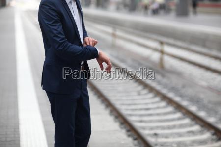 businessman checking time on station platform