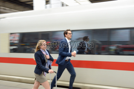 businesswoman and man running for train