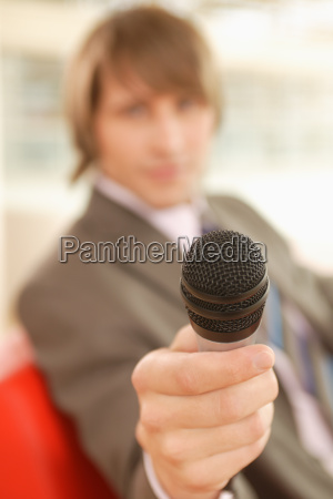 young businessman holding out a microphone