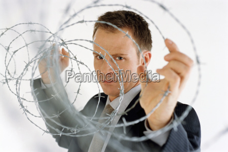 view of businessman holding barbed wire