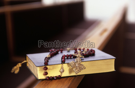 rosary beads on a bible in