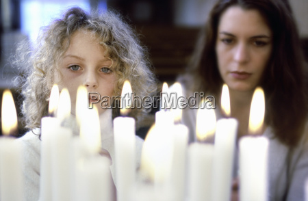 closeup of candles lit with woman
