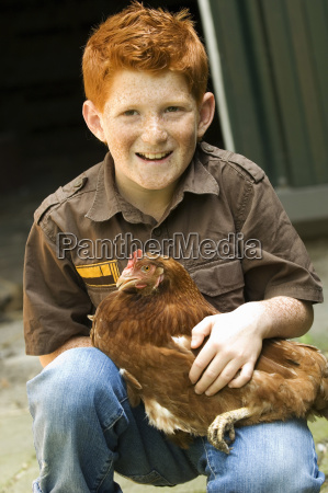 young boy holding chicken outdoors