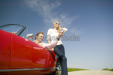 couple and convertible in countryside