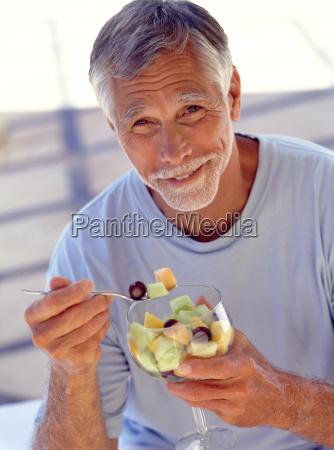 portrait of mature man eating fruit