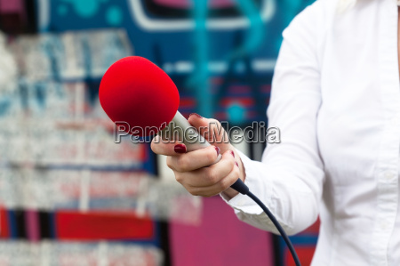journalist holding a microphone conducting an