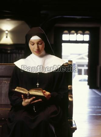 young nun reading bible in church