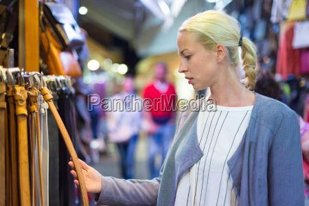 woman shopping for new leather belt