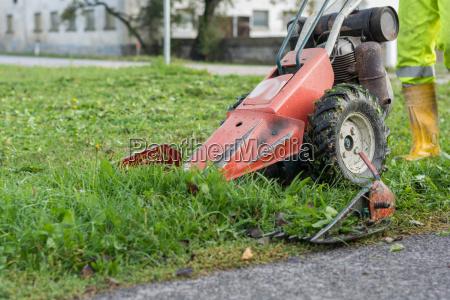 bauer maeht mit balkenmaeher gras
