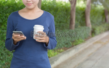 happy woman holding phone and coffee