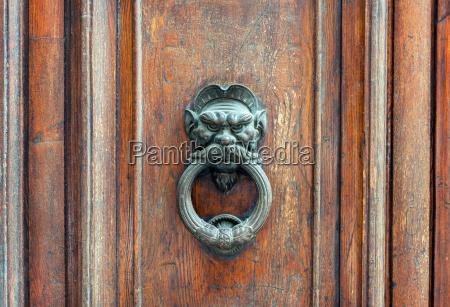 iron lion doorknob on wooden door