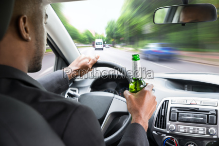 businessman holding beer while driving car