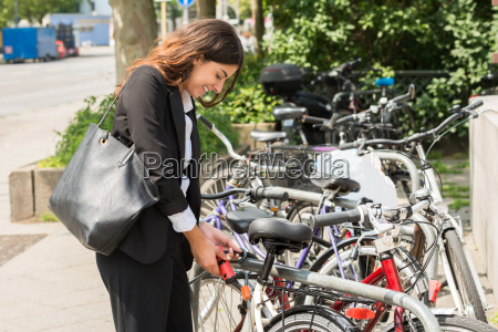 young businesswoman locking up her bicycle