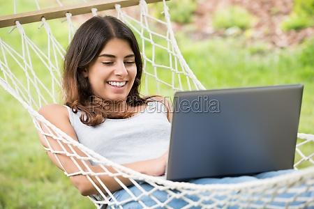 woman lying on hammock using laptop