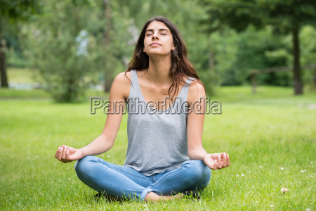woman doing meditation in park