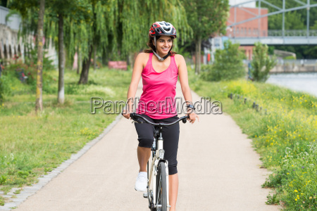 happy young woman riding bicycle