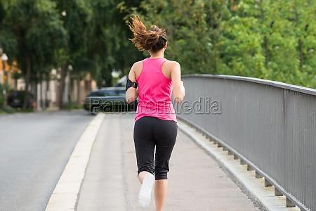fitness woman running on sidewalk