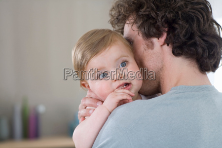 father cuddles baby