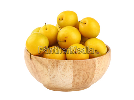 fresh yellow plums in wooden bowl