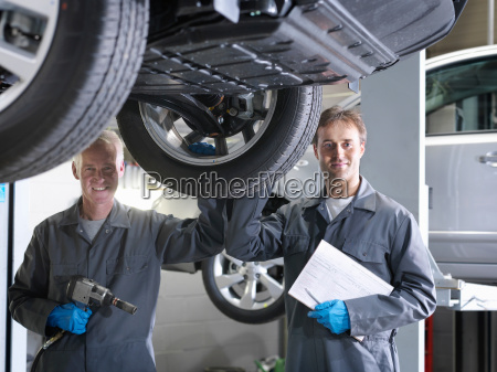 mechanics looking to camera stood next