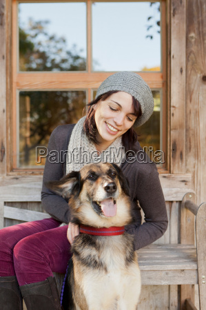 woman petting dog on porch