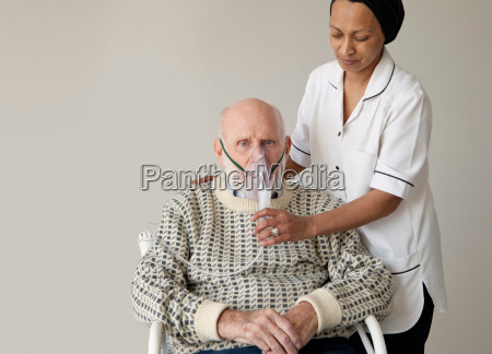 caretaker helping older man with oxygen