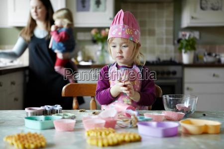toddler girl baking in kitchen