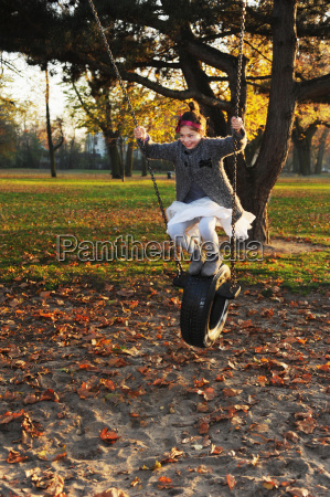 girl playing on tire swing in