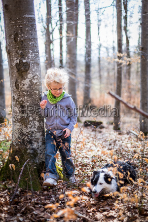 boy and dog exploring in forest