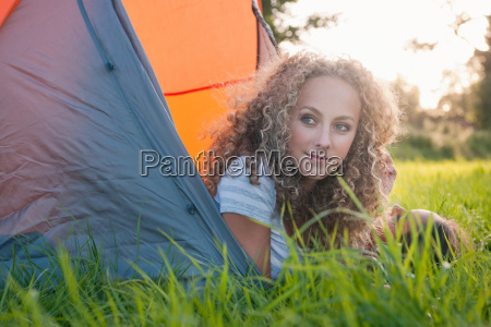teenage girl laying in tent at