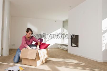 woman unpacking cardboard box in empty