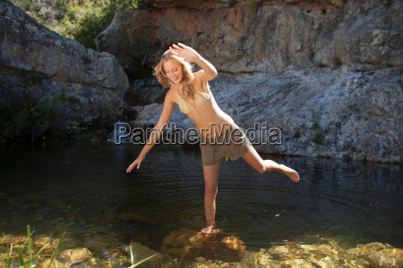 young woman balancing on rock in