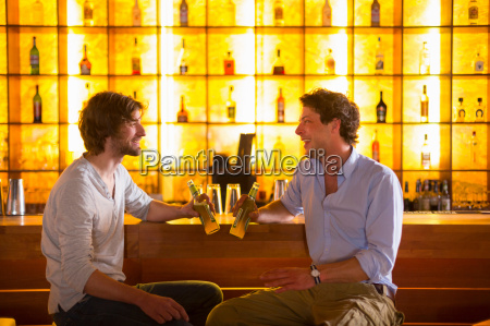 two men sitting at bar with
